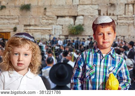 Autumn Jewish holiday Sukkot. The Western Wall of the Temple. Two beautiful Jewish boys in skull-caps with etrog
