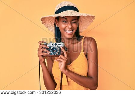 Young african american woman wearing summer hat holding vintage camera winking looking at the camera with sexy expression, cheerful and happy face.