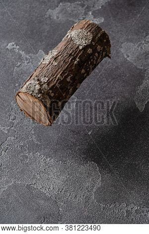 Section of tree trunk hovering over a dark concrete surface.