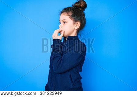 Cute hispanic child wearing casual clothes looking stressed and nervous with hands on mouth biting nails. anxiety problem.