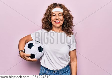 Middle age beautiful sporty woman playing soccer holding football bal over pink background looking positive and happy standing and smiling with a confident smile showing teeth