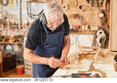 Carpenter master at the workbench when measuring wood with a pencil