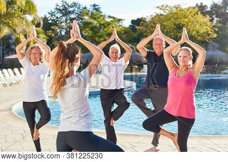 Group seniors on vacation together in the yoga class does the vrksasana exercise