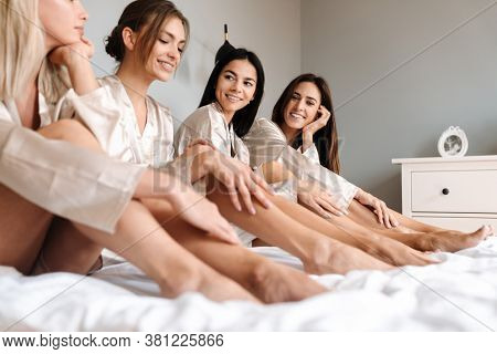 Four attractive young women wearing dressing gowns posing while sitting on bed