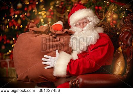 Magical Christmas time. Portrait of a jolly Santa Claus  holding a bag of Christmas gifts. Magic golden lights sparkle around. Christmas and New Year concept.