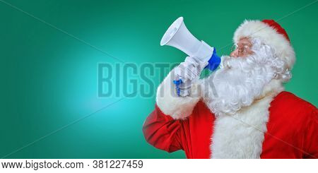 Jolly Santa Claus wishes everyone a Merry Christmas with megaphone in his hand. Studio portrait on a green background.