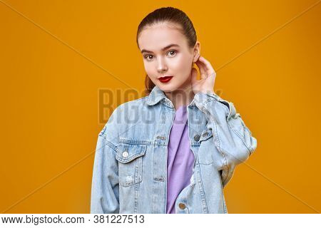 Portrait of a beautiful young woman with natural makeup and red lips in denim jakets on a yellow background. Beauty, makeup, cosmetics.