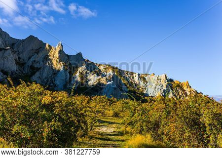 Fabulous country of New Zealand. Dreamland New Zealand. Travel to the South Island. Pointed white Clay cliffs at sunset. Warm sunny day.  High white Clay cliffs with sharp peaks at sunset. Warm sunny