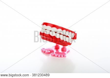 Toy plastic wind up teeth with pink feet on a white background