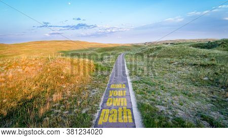 make your own path inspirational text on a narrow, one lane road across sandhills and meadows, career and personal development concept
