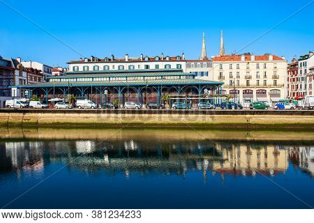 Main Public Market And Colorful Houses At The Nive River Embankment In Bayonne Town In France