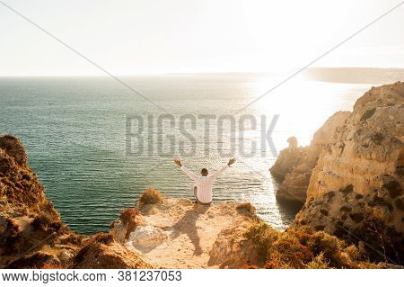 Man Sitting On The Rocks With Open Arms To The Ocean View - Sunset Light