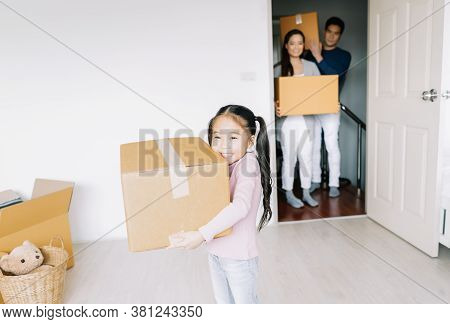 Portrait Of A Happy Asian Little Daughter Carrying Boxes Into The A New Home On Moving Day. Happy Fa