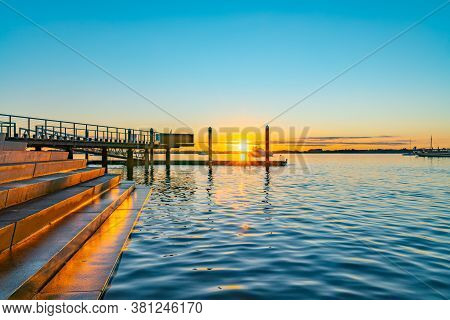 Sunrise Over Blue Water Of Tauranga Harbour With Intense Golden Glow On Horizon With Harbour Steps A