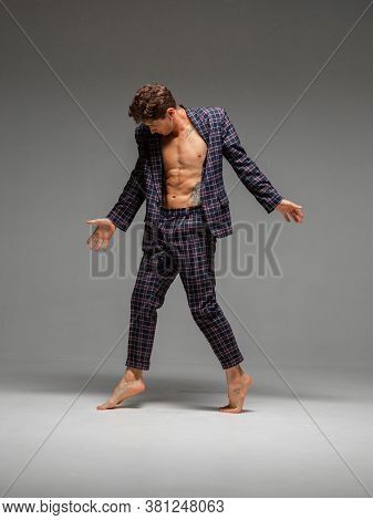 Handsome Young Guy Breakdancer Dancing Expressive Dance In Suit With Naked Torso Isolated On Gray Ba