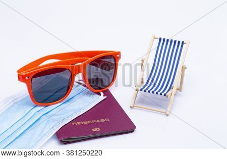 The Photo Shows Sunglasses, Passport, Deck Chair And A Protective Mask