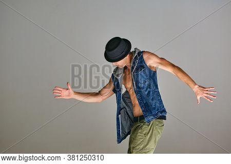 Young Guy Breakdancer In Hat Dancing Hip-hop In Studio Isolated On Gray Background. Dance School Pos