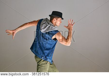 Young Guy Breakdancer In Hat Dancing Expressive Dance In Studio Isolated On Gray Background