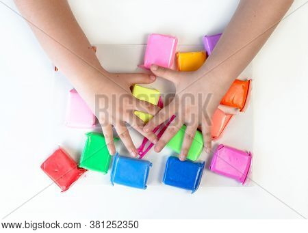 Greedy Child Covers With Hands Multi-colored Plasticine. Multi-colored Airy Clay Mass For Modeling O