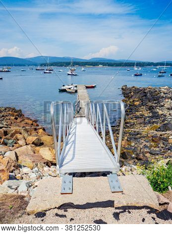 A Boat Ramp Leads Down To A Dock In Southwest Harbor In Maine.  There Are Several Types Of Boats Moo