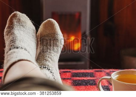 Feet Legs In Winter Clothes Wool Socks And Cup Tea At Fireplace Background. Woman Sitting At Home On