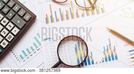 Business Concept With Calculator Glasses Pencil And Magnifying Glass On Documents. Business Grafs An