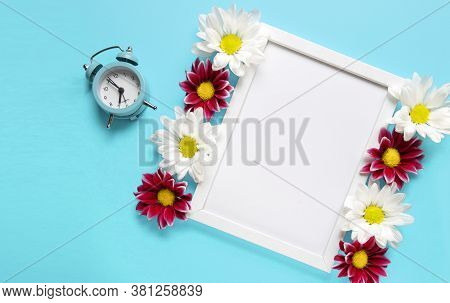 Square White Frame With White And Red Flowers And Blue Alarm Click On Blue Background. View Top. Che