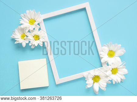 Mockup Square White Frame With White Flowers On Blue Background. View Top. Messege Or Invitation Car