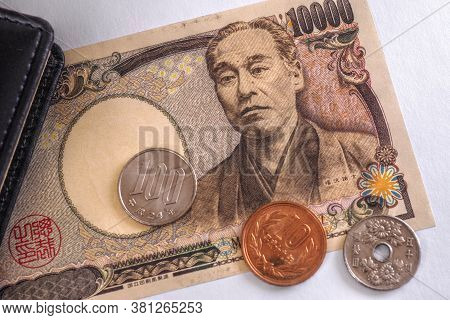 Japanese Money, Notes And Coins Are Near The Diary. 10000 Yen Banknote Close-up. Aged Effect Shot. E