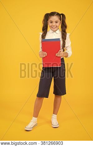 Knowledge Is Light. Adorable Small Girl Holding Book On Yellow Background. Cute Little Child With Sc