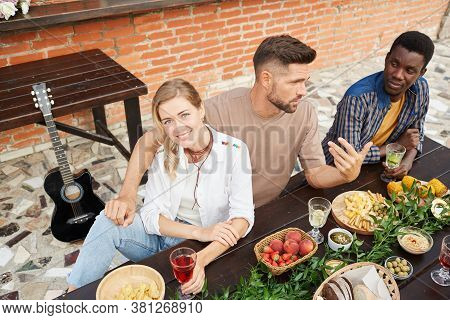High Angle View At Multi-ethnic Group Of Young People Enjoying Dinner Outdoors, Focus On Beautiful W