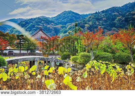 Traditional Japanese Landscape With Shinto Shrine And Red Maple Trees In Foregorund.horizontal Image