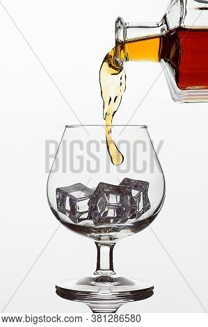 Clear Glass Glass With Ice Cubes. Frozen Stream From A Bottle Of Whiskey Or Cognac Or Brandy On A Wh