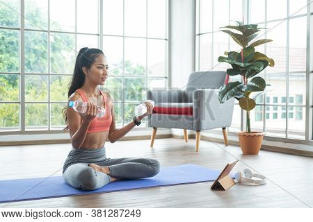 Training At Home. Young Asian Woman Doing Exercises With Water Bottle As Dumbbell While Online Tutor