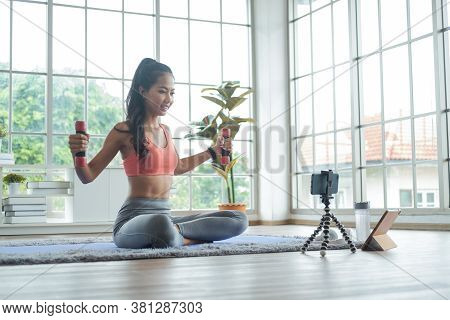 Training At Home. Young Asian Woman Exercise With Dumbbell While Online Tutorial On Mobile Phone.