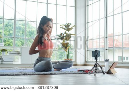 Training At Home. Young Asian Woman Doing Body Stretching While Online Tutorial On Mobile Phone.