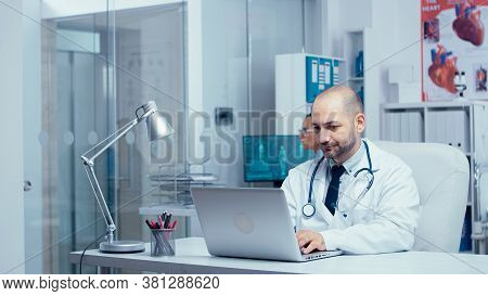 Doctor Typing An E-mail From Modern Office Of Private Clinic With Glass Walls, Nurse In Background C
