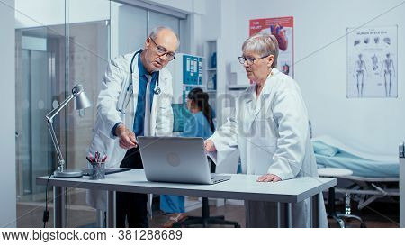 Two Elderly Senior Experienced Doctors Deciding Patient Treatment While Nurse Is Working In Backgrou