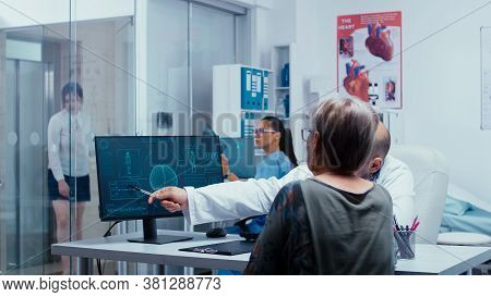 Doctor Presenting Futuristic Medical Brain Scan To Old Retired Woman. Practitioner Explayning Medici