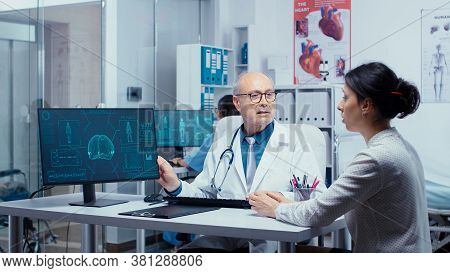 Old Experienced Practitioner Presenting Modern X Ray On Computer Display To Young Patient. Practitio