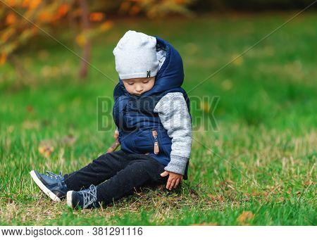 A Small Child Falls Asleep Sitting In The Grass