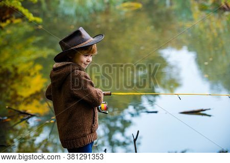 Child Learning How To Fish, Holding A Rod On A Lake. Kid With Fishing Rod. Little Fisherman In A Hat