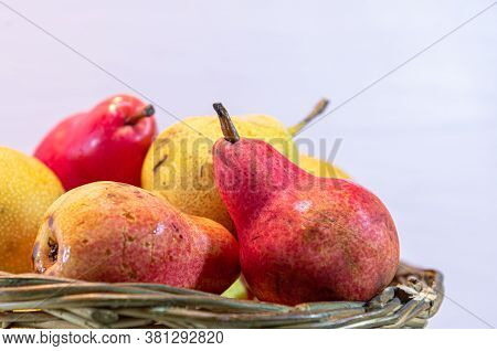 Variety Of Pear Fruits In Wooden Basket On Pink Background