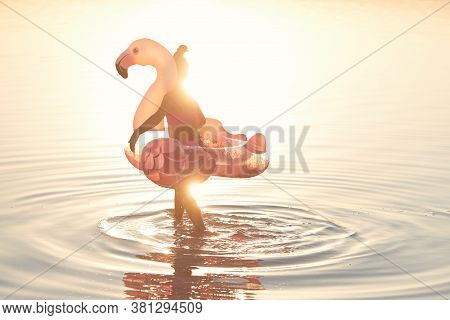 The End Of The Summer. Cute Sad  Child Girl In A Pink Swimsuit Holds An Inflatable Pink Flamingo On
