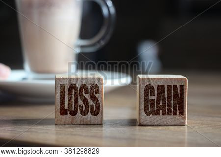Wooden Blocks On Wooden Table With Loss And Gain Words. Money Finance Business Concept.