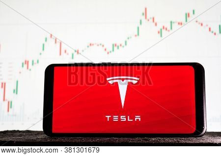 Tula, Russia - August 10, 2020: Logo Tesla On A Smartphone Against The Background Of Stock Market Tr