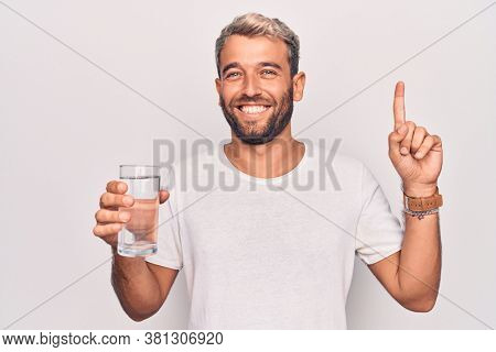 Handsome blond man with beard drinking glass of water to refreshment over white background smiling with an idea or question pointing finger with happy face, number one