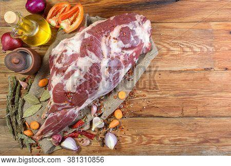 A Raw Leg Of Mutton On A Bone Lies On A Piece Of Burlap , Onions, Garlic, Pepper, Salt, Rosemary And
