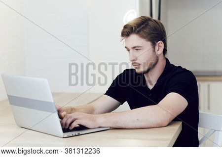 Young Man Working At Home, Typing On Laptop Sitting At Desk. Work At A Distance During Quarantine Of