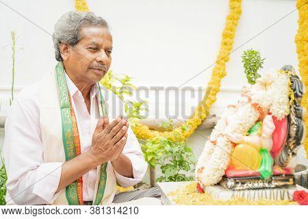 Elder Man Offering Bhajan Or Hymn In Front Of Lord Ganesha Idol During Ganesha Or Vinayaka Chaturthi